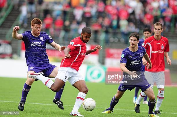 Phil OfosuAyeh of Rot Weiss Erfurt battles for the ball with Niels Hansen and Andreas Glockner of VFL Osnabrueck during the Third League match...