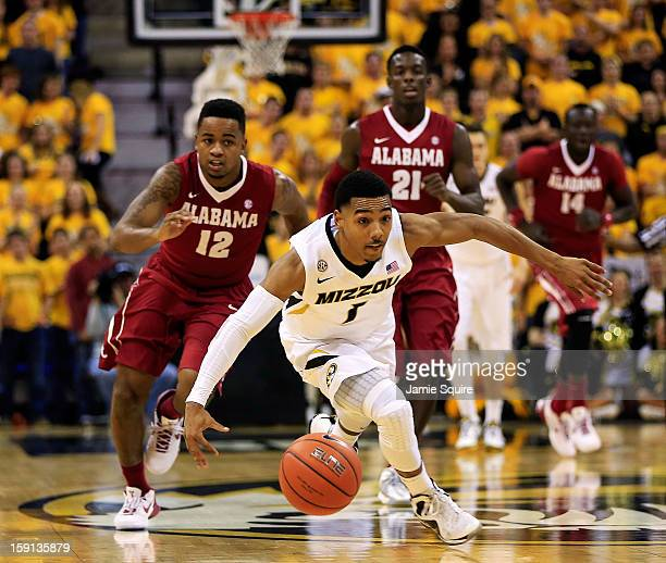Phil Pressey of the Missouri Tigers controls the ball on a fast break as Trevor Releford Rodney Cooper and Moussa Gueye of the Alabama Crimson Tide...