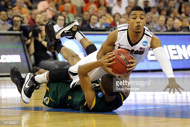 Phil Pressey of the Missouri Tigers fights for control of the ball against Marcos Tamares of the Norfolk State Spartans in the second half during the...