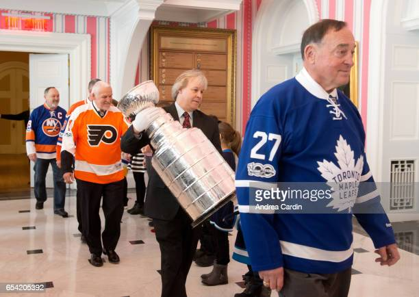 Phil Pritchard curator of the Hockey Hall of Fame carries in the Stanley Cup with Hall of Famers Frank Mahovlich and Bernie Parent during the Stanley...