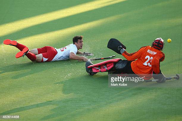 Phil Roper of England dives to score a goal past Andre Rocke of Trinidad and Tobago during the Men's preliminary match between England and Trinidad...