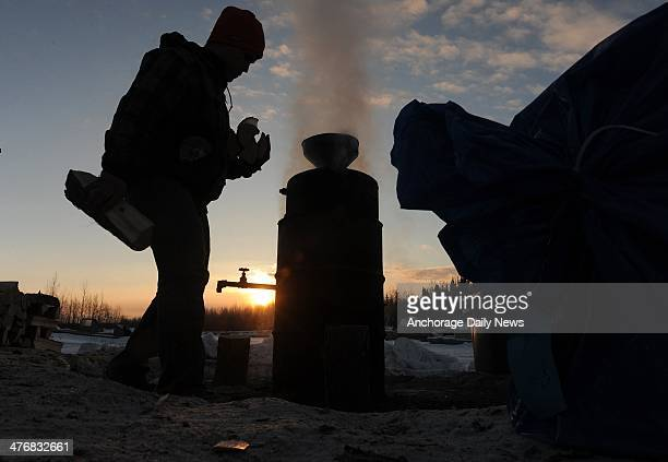 Phil Runkle brings an armful of wood to the water heater at the Nikolai checkpoint during the Iditarod Trail Sled Dog Race at sunrise on Wednesday...