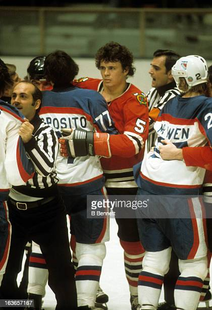 Phil Russell of the Chicago Blackhawks is held back by Phil Esposito of the New York Rangers as linseman John D'Amico holds back a Rangers player...