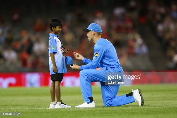 Phil Salt of the Strikers signs a hat for a young fan during the Big Bash League match between the Melbourne Renegades and the Adelaide Strikers at...