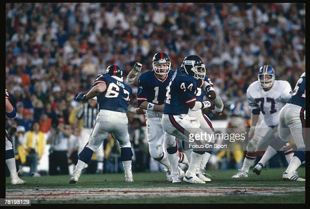 Phil Simms of the New York Giants hands the ball off to Maurice Carthon against the Denver Broncos during Super Bowl XXI on January 26 1987 at the...