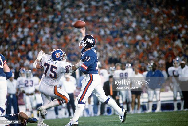 Phil Simms of the New York Giants throws a pass under pressure from Rulon Jones of the Denver Broncos during Super Bowl XXI on January 26 1987 at the...
