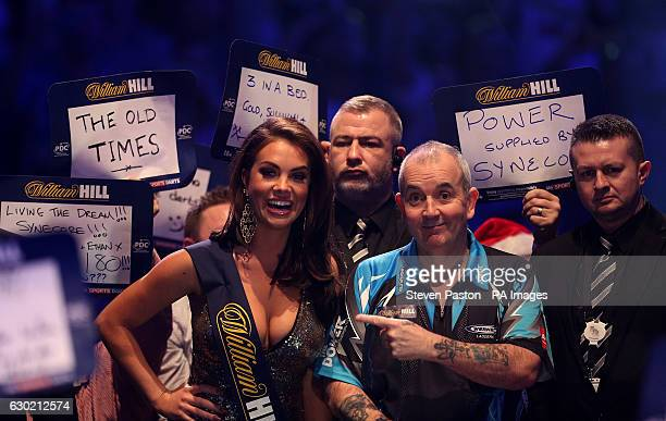 Phil Taylor and a William Hill oche girl during the walk on during day four of the William Hill World Darts Championship at Alexandra Palace London