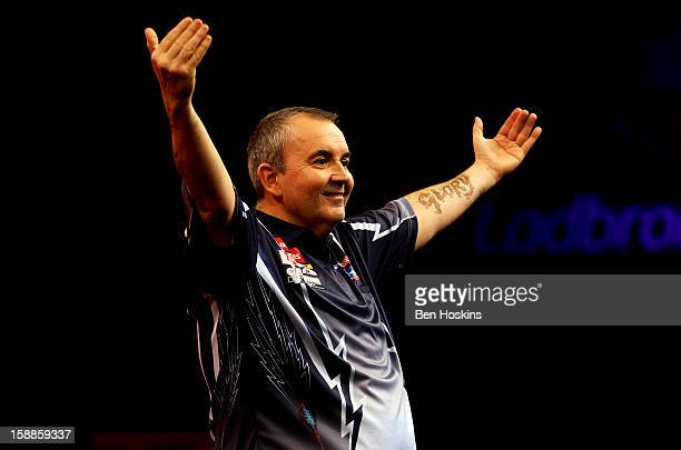 Phil Taylor celebrates winning the tenth set against Michael van Gerwen of the Netherlands during the final of the 2013 Ladbrokescom World Darts...