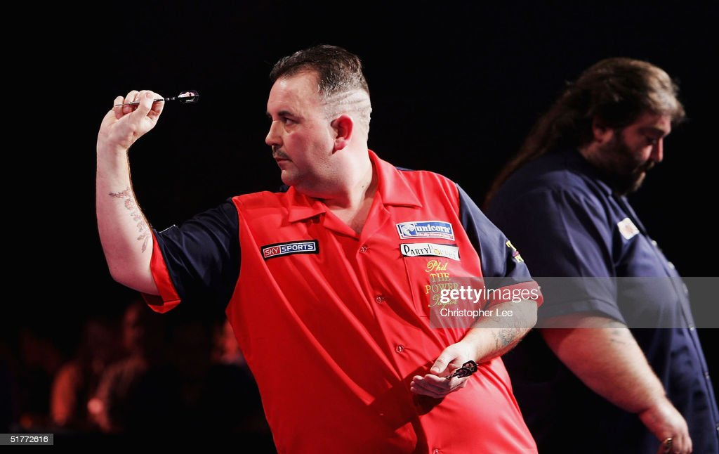 Phil Taylor in action as a dejected looking Andy Fordham walks past during the Showdown match between Phil Taylor and Andy Fordham at The Circus Tavern on November 21, 2004 in Purfleet, England.