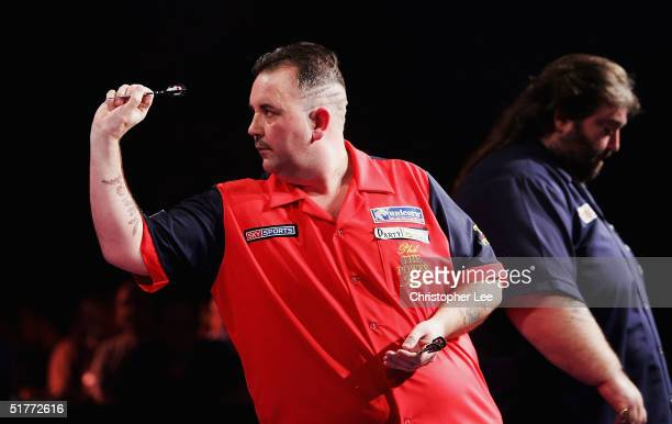 Phil Taylor in action as a dejected looking Andy Fordham walks past during the Showdown match between Phil Taylor and Andy Fordham at The Circus...