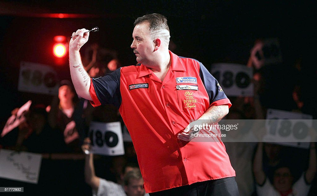 Phil Taylor in action as the fans celebrate Andy Fordham scoring a 180 during their showdown match at The Circus Tavern on November 21, 2004 in Purfleet, England.