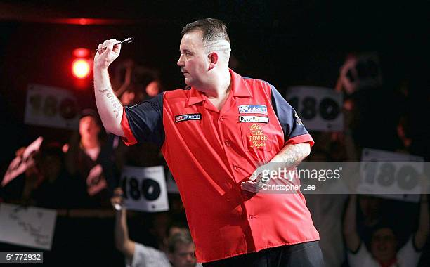 Phil Taylor in action as the fans celebrate Andy Fordham scoring a 180 during their showdown match at The Circus Tavern on November 21 2004 in...
