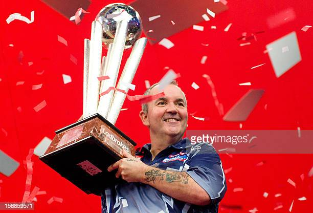 Phil Taylor of Britain celebrates with the Sid Waddell trophy after defeating Michael van Gerwen of the Netherlands in the PDC World Championship...