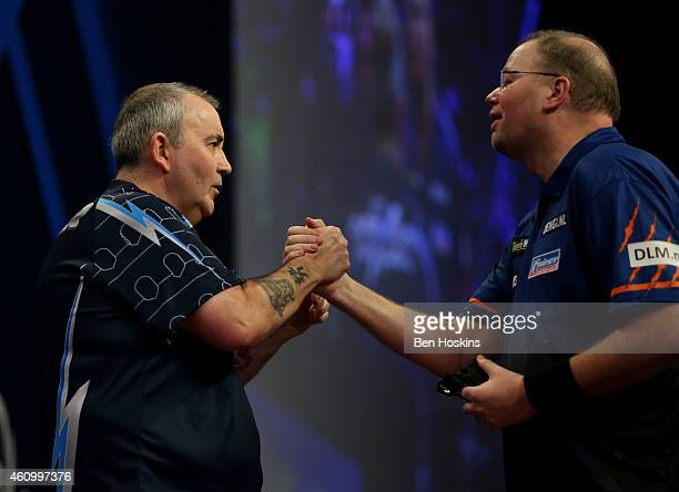 Phil Taylor of England and Raymond van Barneveld of the Netherlands shake hands after their semi final match on day thirteen of the 2015 William Hill...