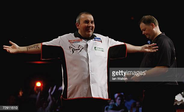 Phil Taylor of England celebrates a point against Raymond Van Barneveld of Holland Britain during the finals of the Ladbrokes World Darts...