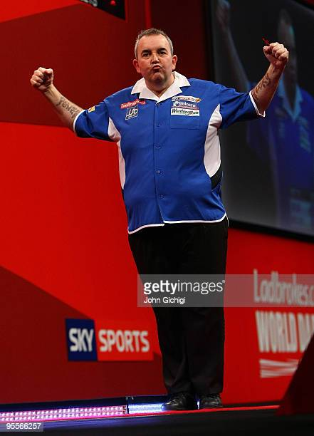 Phil Taylor of England celebrates a point in the game against Simon Whitlock of Australia during the Final of the Ladbrokescom World Darts...