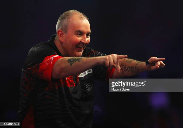 Phil Taylor of England celebrates after scoring 180 during the PDC World Darts Championship final against Rob Cross of England on Day Fifteen at the...