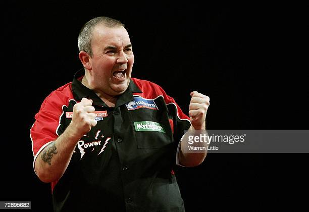 Phil Taylor of England celebrates beating Chris Mason of England during the third round of The Ladbrokes World Darts Championship at The Circus...