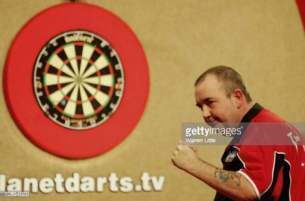 Phil Taylor of England celebrates winning a leg against Chris Mason of England during the third round of The Ladbrokes World Darts Championship at...