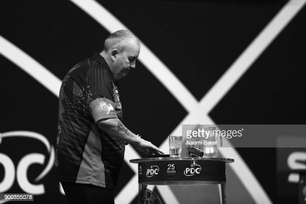 Phil Taylor of England collects his darts during the PDC World Darts Championship final against Rob Cross of England on Day Fifteen at the 2018...
