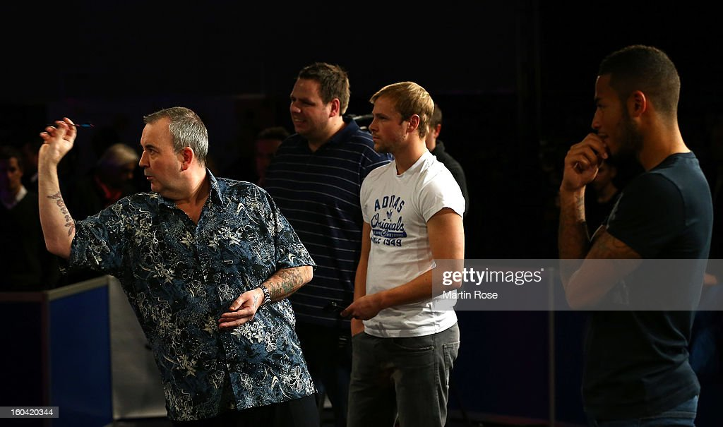 Phil Taylor of England in action during a dart show tournament at between team England and Hamburger SV at Imtech Arena on January 31, 2013 in Hamburg, Germany.