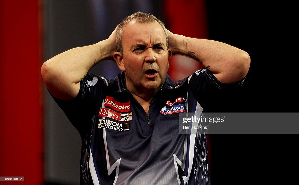 Phil Taylor of England reacts during his semi final match against Raymond van Barneveld of the Netherlands on day fourteen of the 2013 Ladbrokes.com World Darts Championship at the Alexandra Palace on December 30, 2012 in London, England.