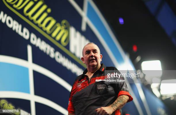 Phil Taylor of England walks off the stage after a set during the PDC World Darts Championship final against Rob Cross of England on Day Fifteen at...