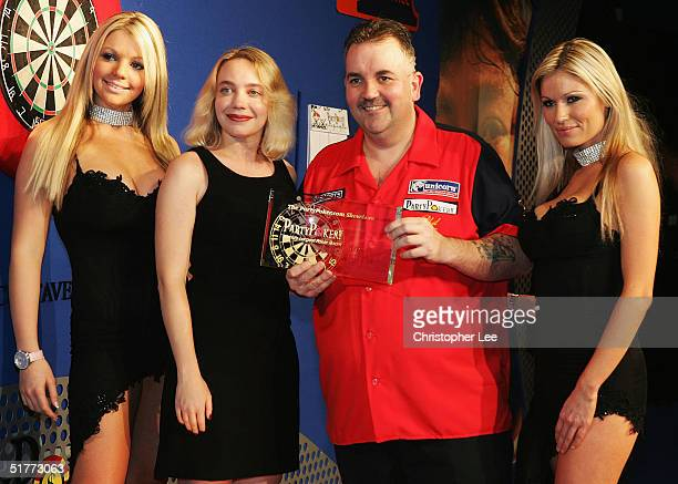Phil Taylor poses with his prize after Andy Fordham conceded due to illness during the Showdown match at The Circus Tavern November 21 2004 in...