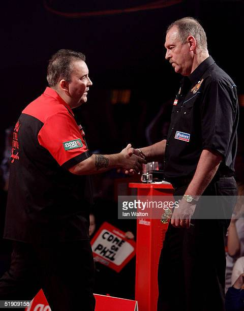 Phil Taylor shakes hands with Bob Anderson after winning the match during the 2005 Ladbrokescom World Darts Championship at The Circus Tavern on...