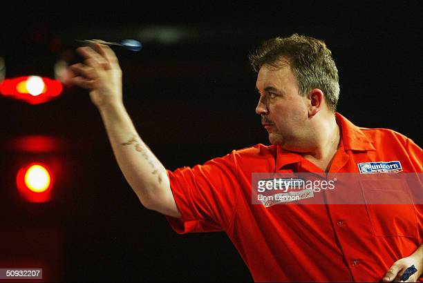 Phil Taylor throws against John Part during the quarterfinals of the Budweiser UK Open Darts Championship at the Reebok Stadium on June 6, 2004 in...