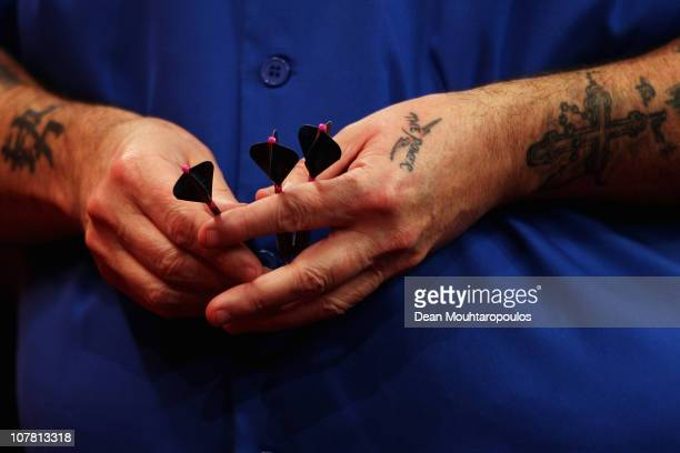Phil 'The Power' Taylor of England holds his darts against Peter Wright of England during day 11 in the 2011 Ladbrokescom World Darts Championship at...