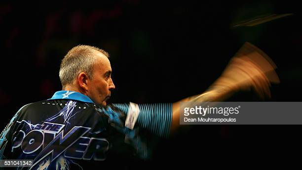 Phil 'The Power' Taylor of England plays a shot in his match against Michael van Gerwen of the Netherlands during the Darts Betway Premier League...