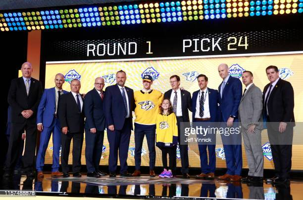Phil Tomasino, 24th overall pick of the Nashville Predators, poses for a photo onstage with team personnel during the first round of the 2019 NHL...