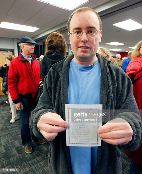 Phil Zoeller holds up his blank voters ballot as he prepare to cast his vote in the GOP presidential caucus at the University of Louisville campus...