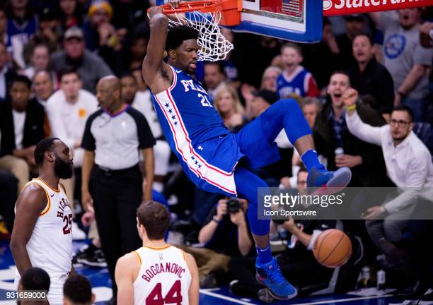 Philadelphia 76ers Center Joel Embiid hangs onto the rim after a dunk in the second half during the game between the Indiana Pacers and Philadelphia...