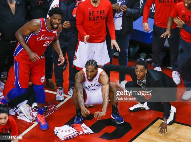 Philadelphia 76ers center Joel Embiid watches from the corner as Toronto Raptors forward Kawhi Leonard squats down and sticks out his tongue waiting...