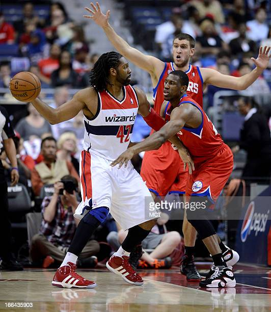 Philadelphia 76ers center Spencer Hawes back and 76ers small forward Thaddeus Young right defend Washington Wizards center Nene Hilario in the first...