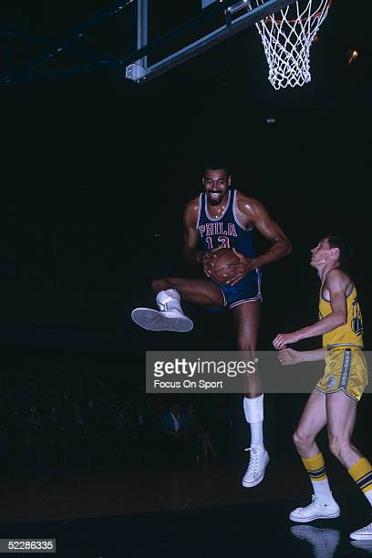 Philadelphia 76ers' center Wilt Chamberlain jumps and grabs the rebound during a game circa 1960's against the Golden State Warriors.