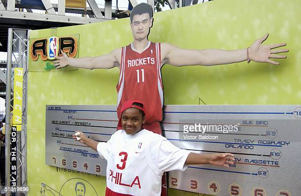 Philadelphia 76ers fan compares his arm length to Yao Ming's arm span during the NBA Rhythm 'n Rims presented by Sprite the NBA's interactive...