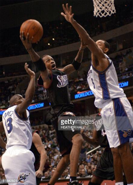 Philadelphia 76ers' guard Allen Iverson drives the lane for a basket against Washington Wizards' Felipe Lopez and Juwan Howard in the second quarter...