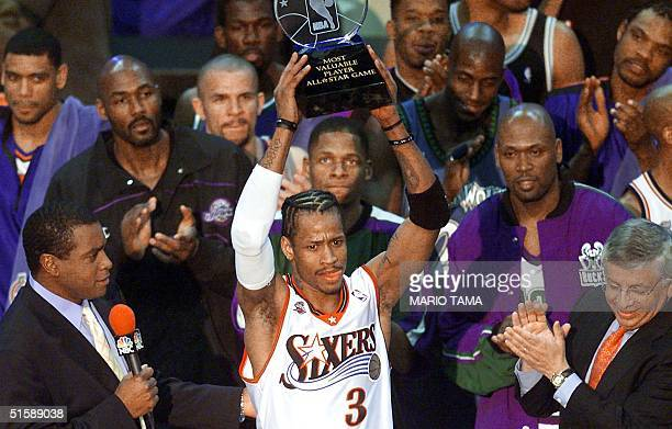 Philadelphia 76ers' guard Allen Iverson stands among his fellow NBA AllStars and holds his MVP trophy for his performance in the 2001 NBA AllStar...
