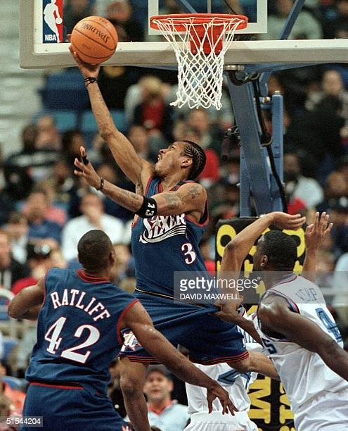 Philadelphia 76ers' guard Allen Iverson tosses in a driving layup as Cleveland Cavaliers' forward Shawn Kemp holds on to his jersey befor 76ers' Theo...