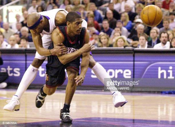 Philadelphia 76ers' Kevin Ollie passes the ball while Toronto Raptors' Vince Carter hitches a ride during second half action of game four of the...