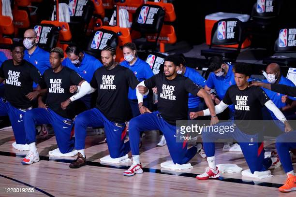Philadelphia 76ers players kneel in honor of the Black Lives Matter movement during the national anthems prior to an NBA game against the Toronto...