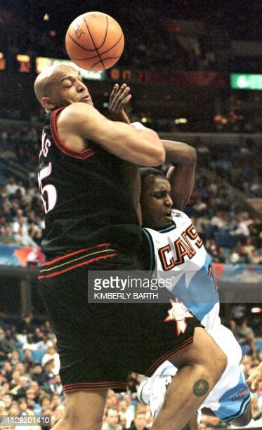 Philadelphia 76'ers Scott Williams blocks Cleveland Cavaliers guard Brevin Knight as he drives the lane for a basket in the first half 11 April at...