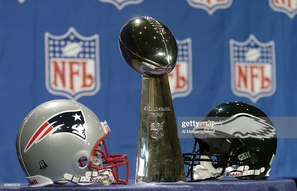 Philadelphia Eagles And New England Patriots Helmets Face Off With The Vince Lombardi Trophy At NFL
