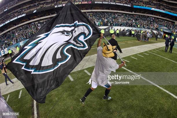 Philadelphia Eagles cornerback Jalen Mills wears a dog mask and runs with the Philadelphia Eagles flag in celebration with fans and teammates after...