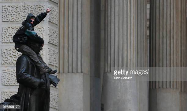 Philadelphia Eagles fan climbs onto of a statue of John Wanamaker in front of City Hall during the team's Super Bowl Victory Parade on February 8...