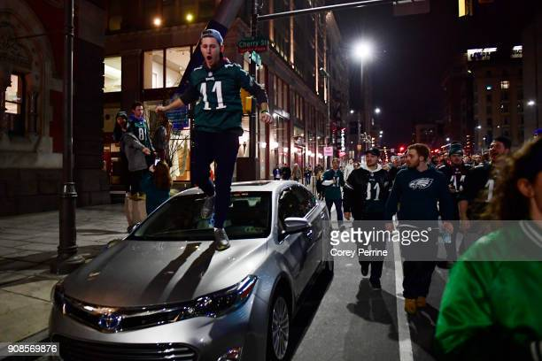 Philadelphia Eagles fan runs on top of a car celebrating North Broad Street with droves of others downtown near City Hall on January 21 2018 in...