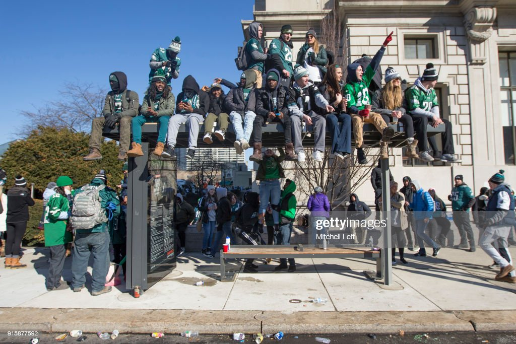 Philadelphia Eagles fans watch the Super Bowl LII parade from a bus stop waiting area on February 8, 2018 in Philadelphia, Pennsylvania.